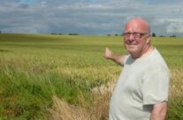 A personal visit for Russell Davies, pointing to the field in which his Grandfather died on the Somme – Somme Battlefield Tour