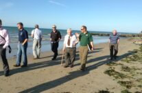 Tony Eden of Rifleman Tours walks our WW2 Veteran Bill and the group along Gold Beach – Normandy & D-Day Landings 70th Anniversary Ceremony & Battlefield Tour